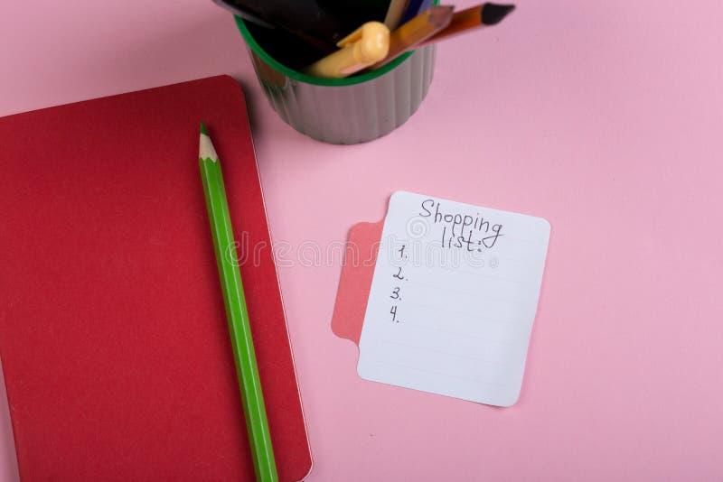 与手写的文本购物清单、笔记薄和铅笔的贴纸在桃红色背景 图库摄影