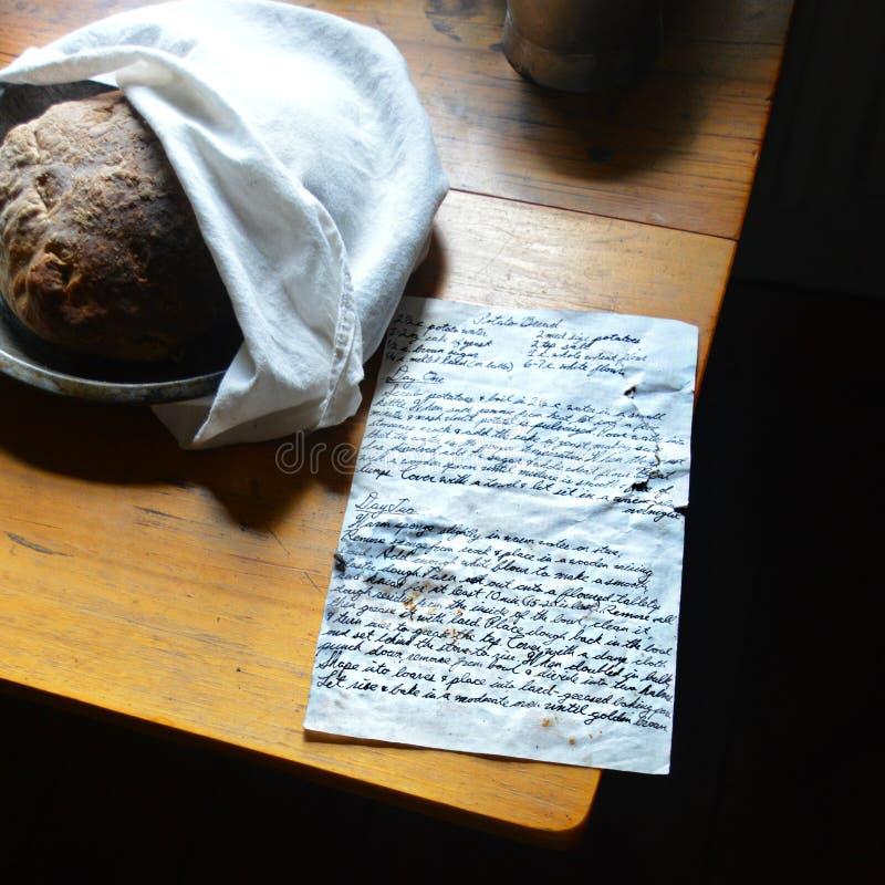 与手写的食谱的土豆面包 免版税库存照片