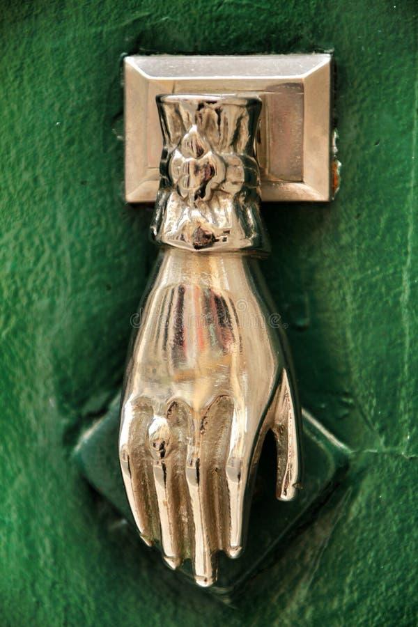 与手形状的通道门环在绿色木门 免版税图库摄影