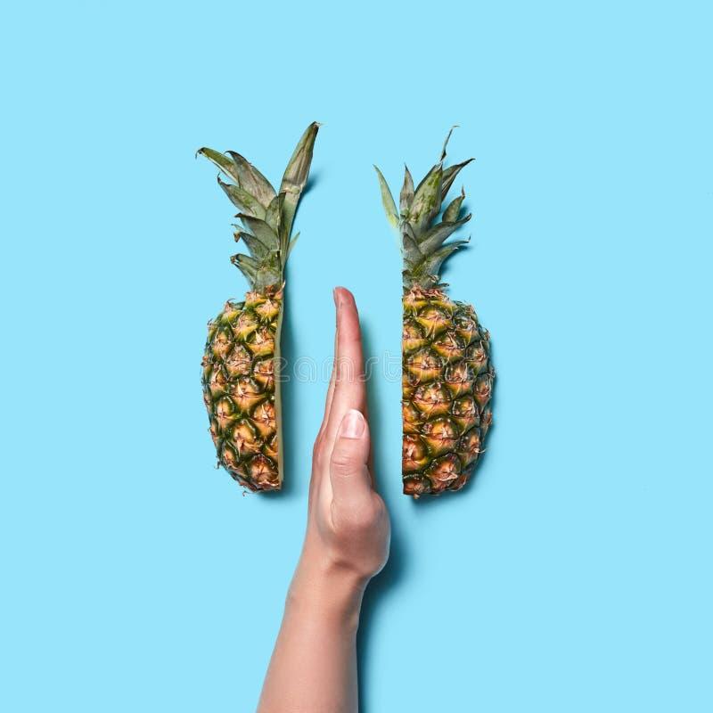 与手指一半的女性手零件在蓝色背景的菠萝与文本的空间 平的位置 库存照片