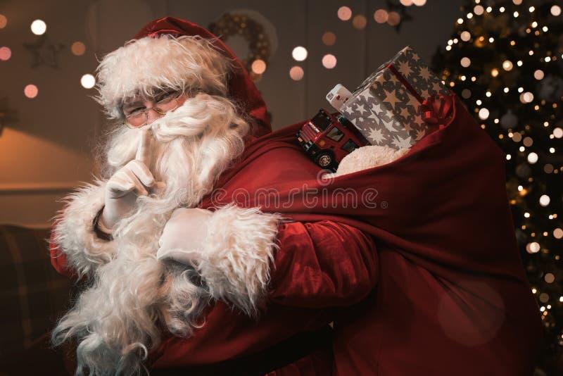 与手指的圣诞老人项目在嘴唇 库存图片