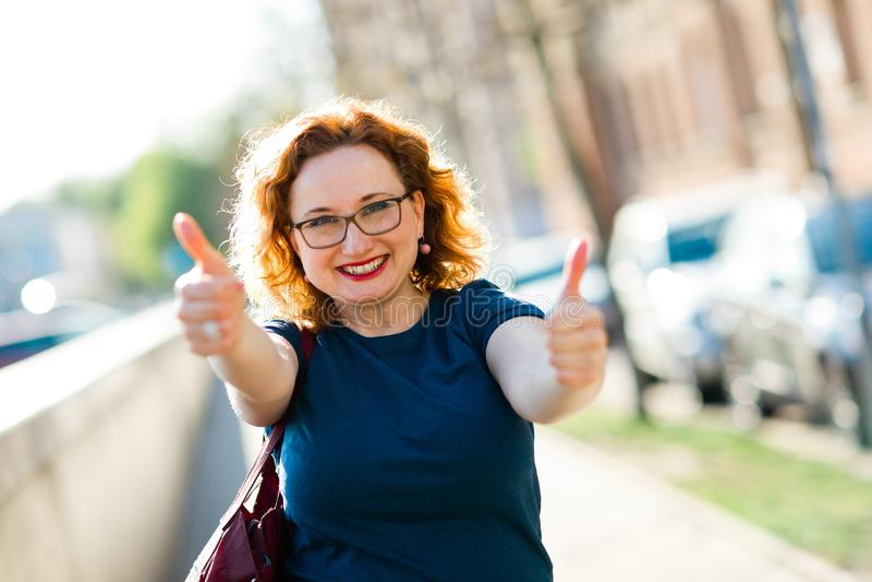 与手指的有吸引力的妇女陈列姿态-赞许 免版税库存图片