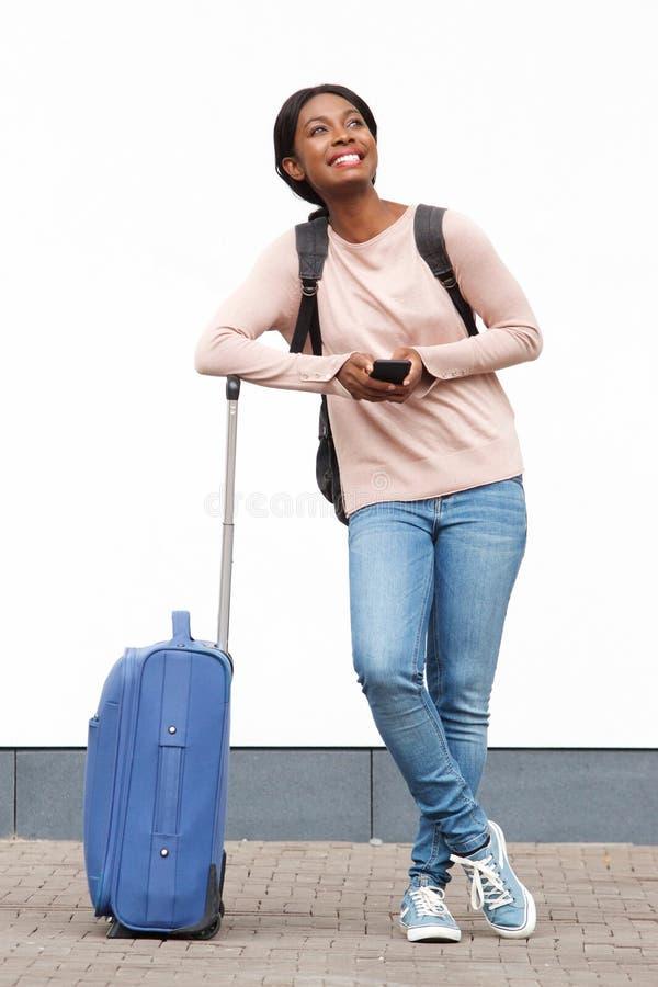 与手提箱和手机的全长微笑的年轻非裔美国人的妇女身分对白色墙壁 免版税图库摄影