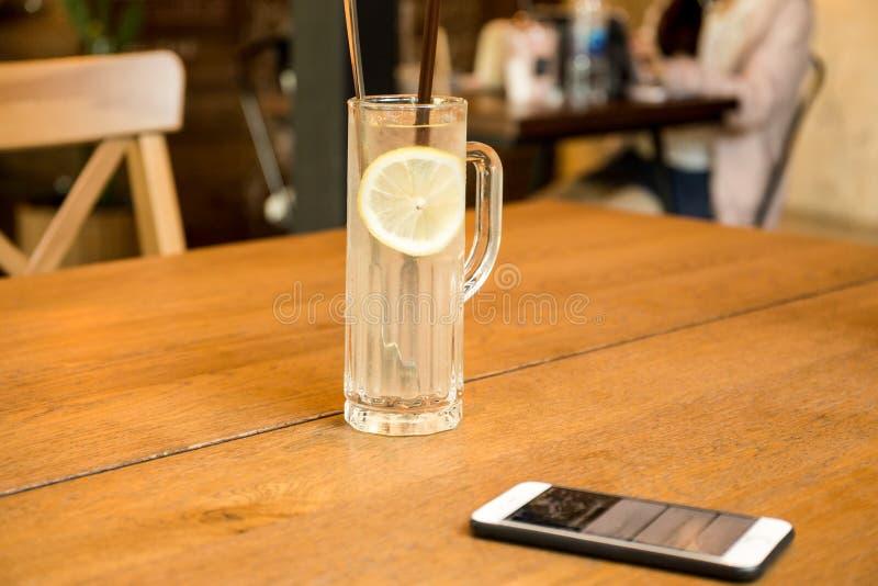 与手机的医疗保健新柠檬汁饮料在木ta 免版税库存照片