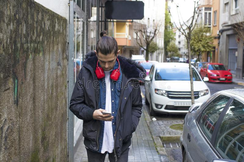 与手机的年轻人在街道上 免版税库存照片