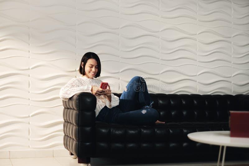 与手机的年轻西班牙女孩传讯在沙发 免版税库存图片
