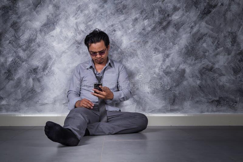 与手机的沮丧的商人和坐地板 免版税库存图片