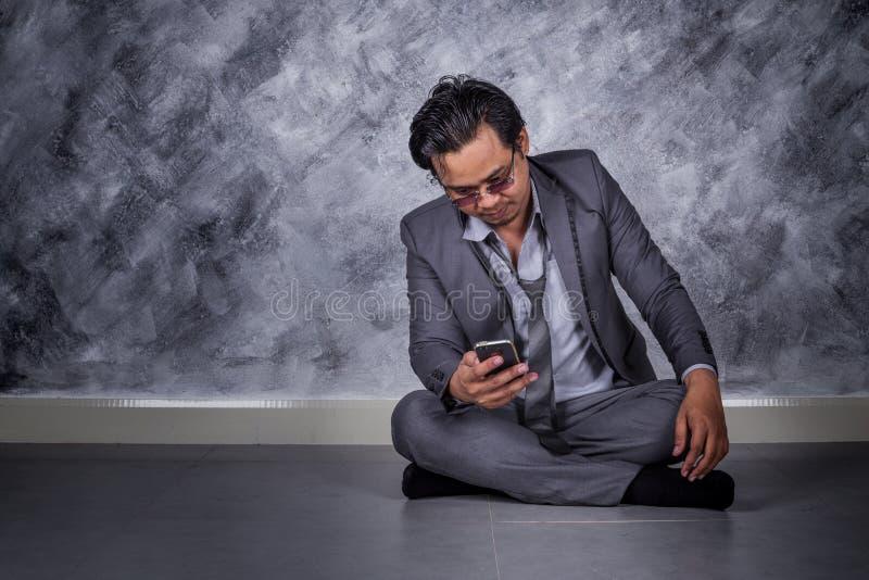 与手机的沮丧的商人和坐地板 库存图片