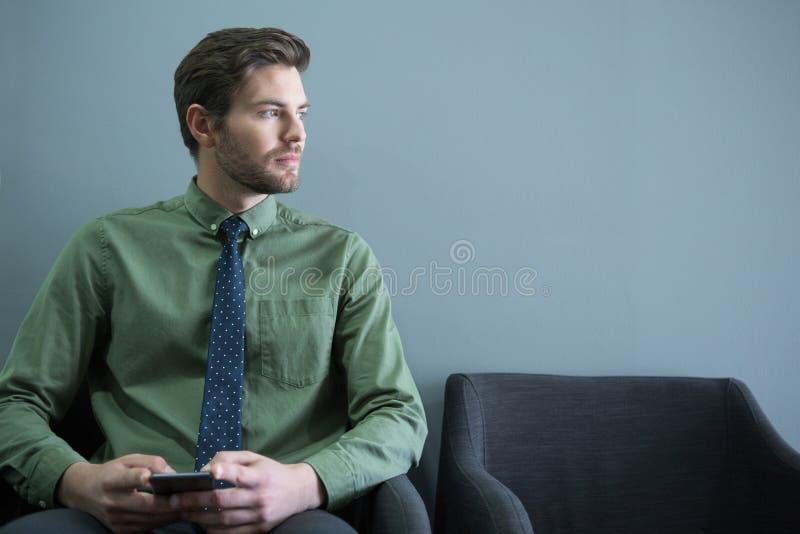 与手机的男性行政开会在等候室 库存图片
