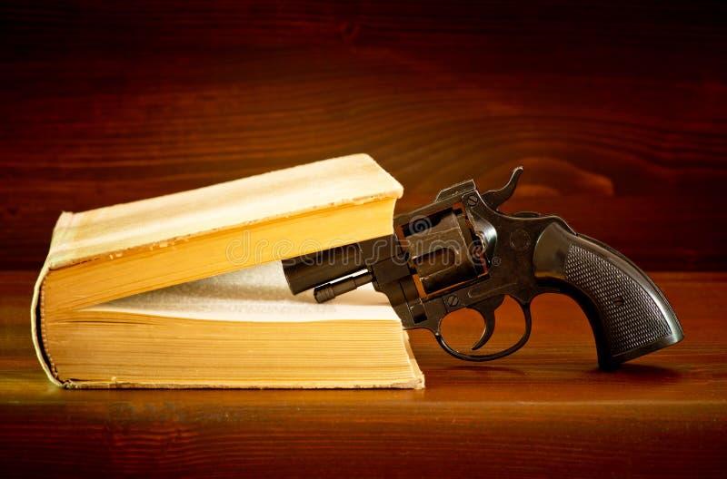 与手枪的书 免版税库存图片
