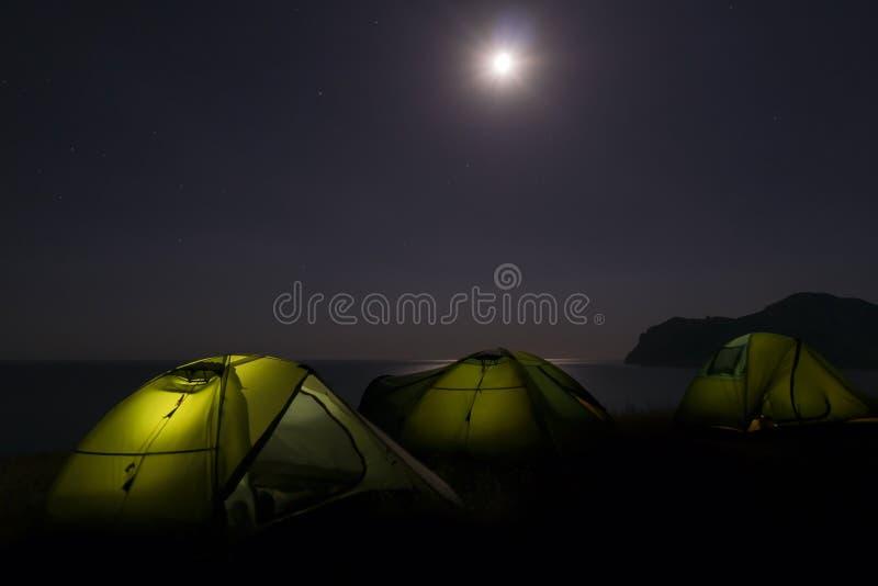 与手电光的迁徙的帐篷阵营里面在黑暗的夜空和满月下 旅行野营的设备为 库存照片
