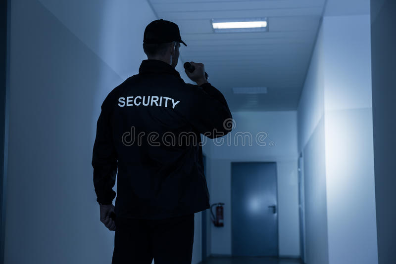 与手电的治安警卫在大厦走廊 库存照片