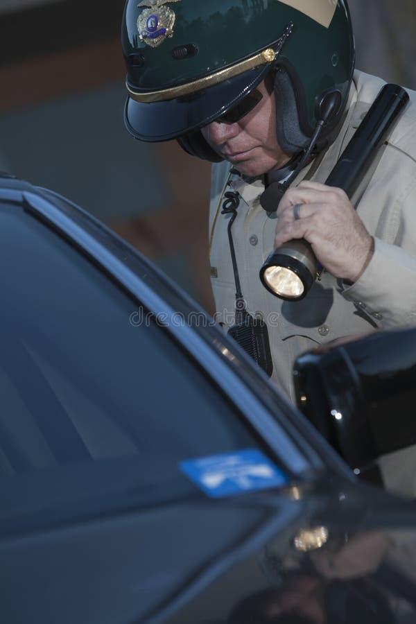 与手电调查的汽车的警察 库存图片