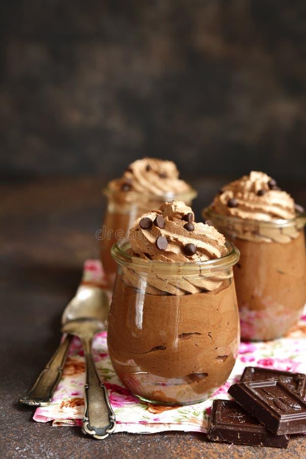 与打好的奶油的巧克力沫丝淋在葡萄酒玻璃瓶子 库存照片
