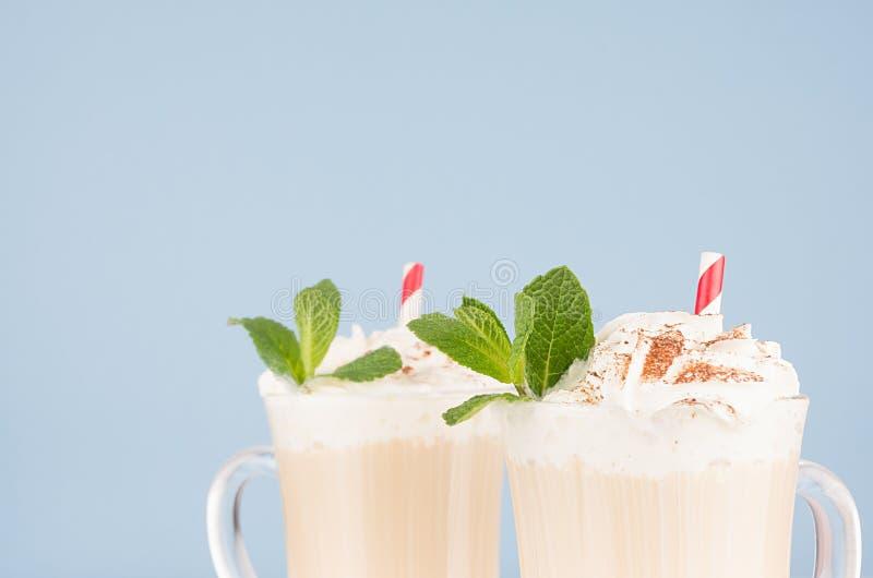 与打好的奶油,绿色薄菏,巧克力粉末,在玻璃特写镜头,细节,关于浅兰的顶面部分的秸杆的新咖啡饮料 免版税库存图片