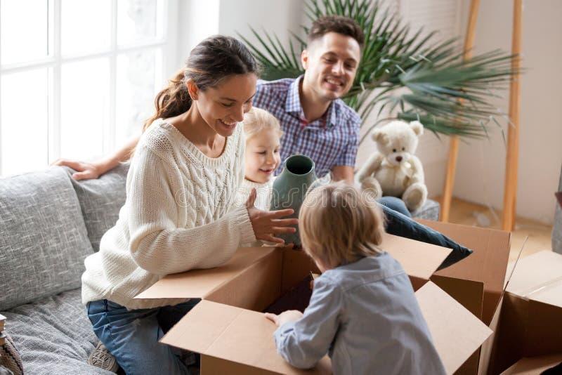 与打开箱子的孩子的愉快的家庭搬入新的家 免版税图库摄影