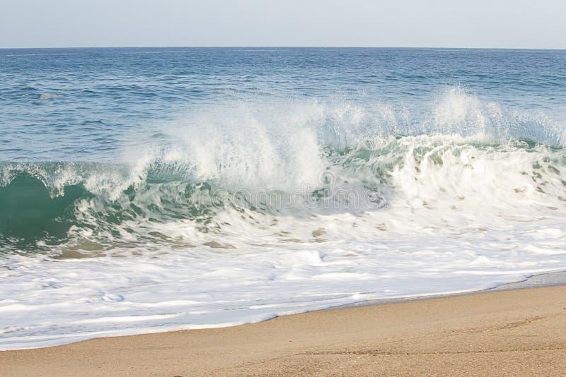 与打破在含沙海岸线的回流泡沫的Backspray顶饰的波浪 库存照片