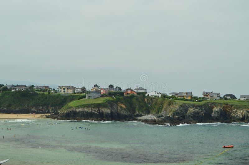 与打破在它的在议院背景人群的岩石的波浪的海湾在峭壁上的在塔皮亚德卡萨列戈 库存照片