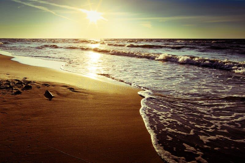 与打破在海滩的波浪的波罗的海海岸在日落 风景美丽如画的夏天海景 免版税库存照片