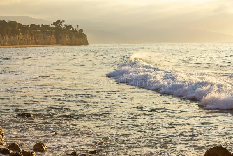 与打破横跨与岩石海岸线,penninsulla,沙滩的海湾的回流的起泡沫的波浪 库存照片
