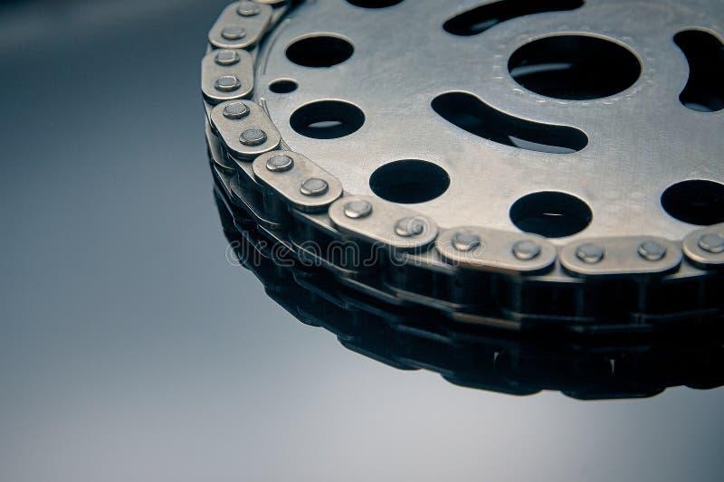与扣练齿轮的路辗链子在黑暗的背景 它使用在汽车,摩托车,自行车和在机械工程方面 库存照片