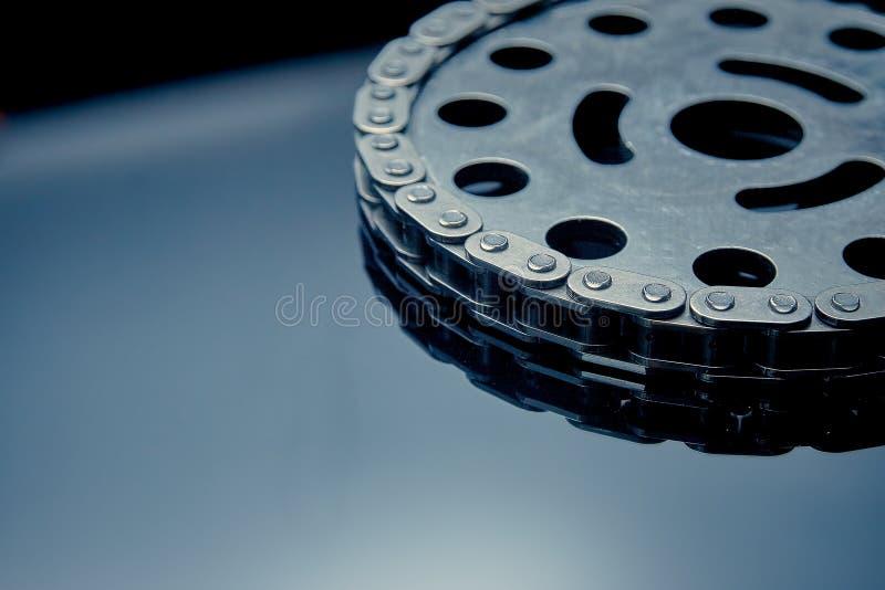 与扣练齿轮的路辗链子在黑暗的背景 它使用在汽车,摩托车,自行车和在机械工程方面 免版税图库摄影