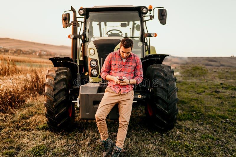 与技术和机械概念的现代农业 使用智能手机和拖拉机的微笑的农夫画象在收获 库存照片