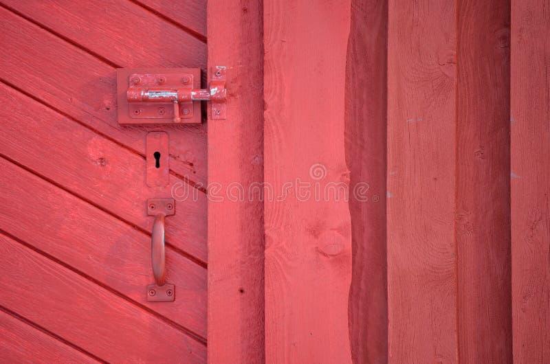 与把柄的红色毂仓大门和关键孔和deadbolt锁 免版税库存图片