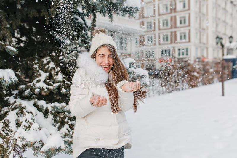 与把雪和笑扔出去的长发的梦想的女性模型 享受圣诞节打过工的令人惊讶的欧洲女孩和 库存照片