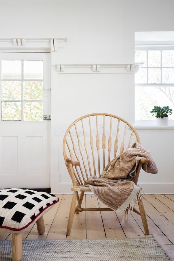 以与投掷和坐垫无背长椅的木胳膊椅子为特色分开 免版税库存图片
