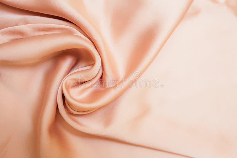 与折叠和wawes的光滑的biege织品布料纹理 抽象背景的关闭 Biege drapped丝绸 免版税库存照片
