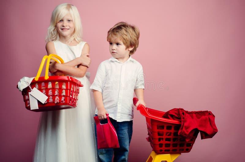 与折扣的购买 女孩和男孩儿童购物 夫妇孩子拿着塑料手提篮玩具 孩子商店 r 免版税图库摄影