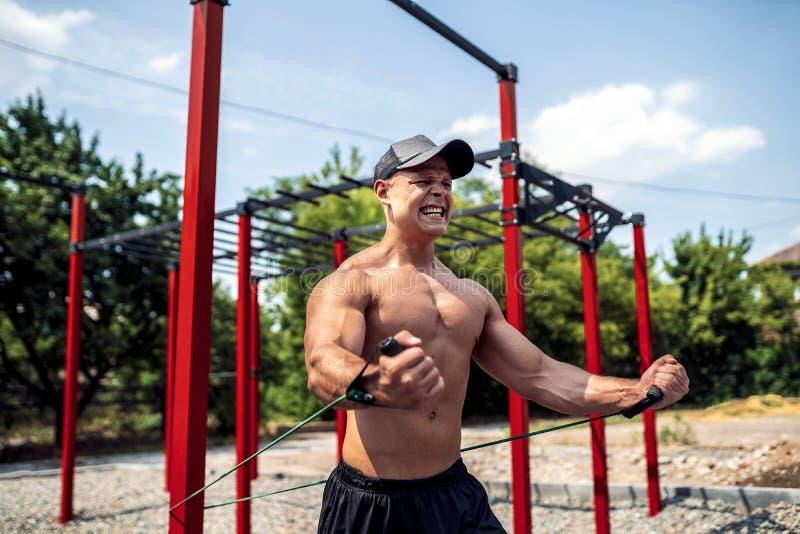 与抵抗带的健身人训练胸口在街道健身房围场 室外锻炼 身体锻炼用设备 库存照片
