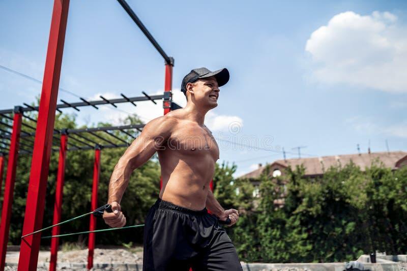 与抵抗带的健身人训练胸口在街道健身房围场 室外锻炼 身体锻炼用设备 库存图片