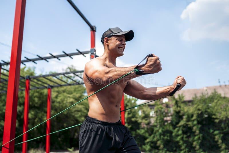 与抵抗带的健身人训练胸口在街道健身房围场 室外锻炼 身体锻炼用设备 免版税库存照片