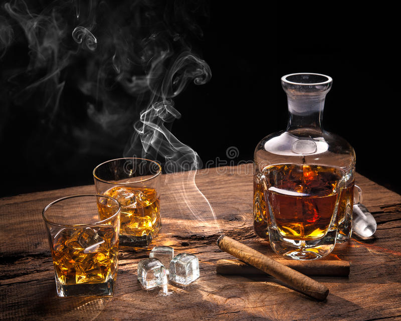 与抽烟的雪茄的威士忌酒 免版税库存图片