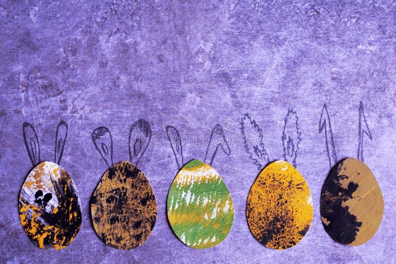 与拉长的兔宝宝耳朵的五个装饰五颜六色的纸鸡蛋 免版税库存照片
