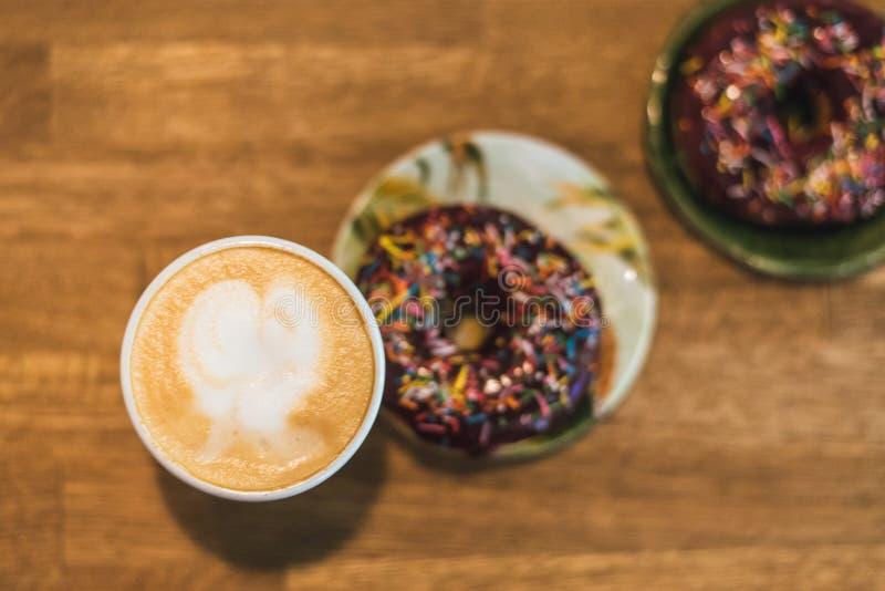 与拉长的心脏和牛奶的咖啡在一张木桌上在咖啡馆 与驱散的两个巧克力油炸圈饼在桌上在旁边 库存照片