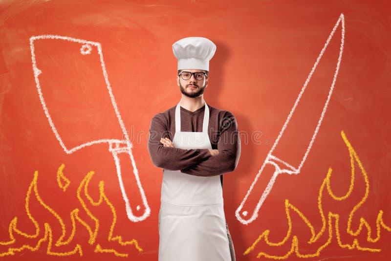与拉长的火焰、一把砍肉刀、一把刀子和一个严肃的男性厨师身分的明亮的橙色背景在中心 库存图片