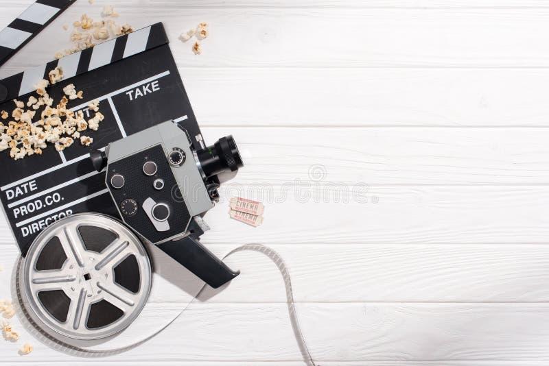 与拍板、filmstrips、减速火箭的照相机和戏院票的平的位置安排了白色木表面上 库存图片