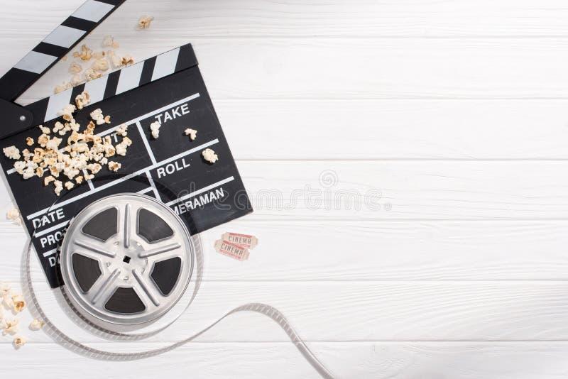 与拍板、filmstrips、玉米花和减速火箭的戏院票的平的位置在白色木桌面安排了 免版税库存照片