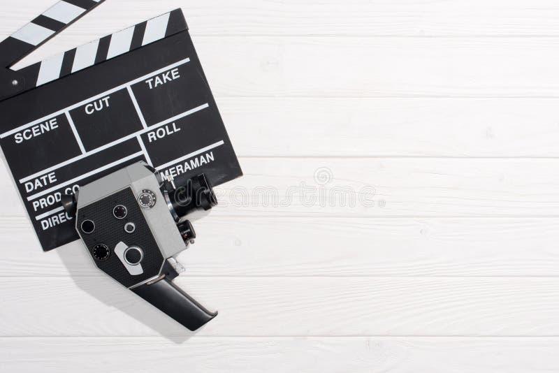 与拍板和减速火箭的照相机的平的位置在白色木桌面 图库摄影