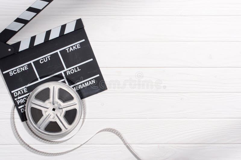 与拍板的平的在白色木桌面的位置和filmstrips 库存照片