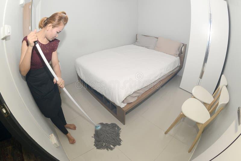 与拖把清洁地板的亚洲佣人清洁服务在卧室 图库摄影