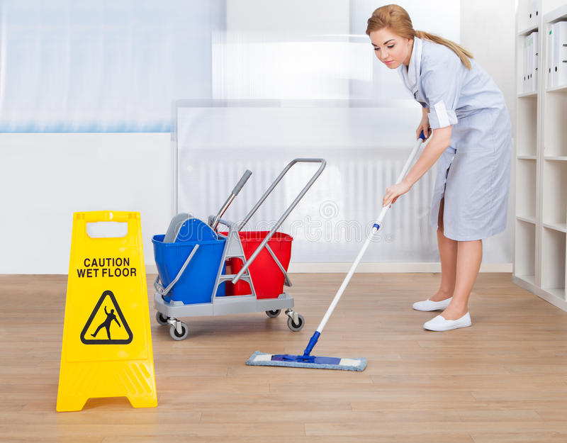 与拖把的愉快的佣人清洁地板 免版税库存照片