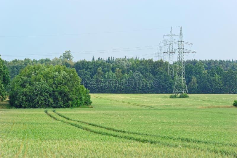 与拖拉机轨道和高压塔,在遥远的电定向塔的绿色领域 免版税库存图片