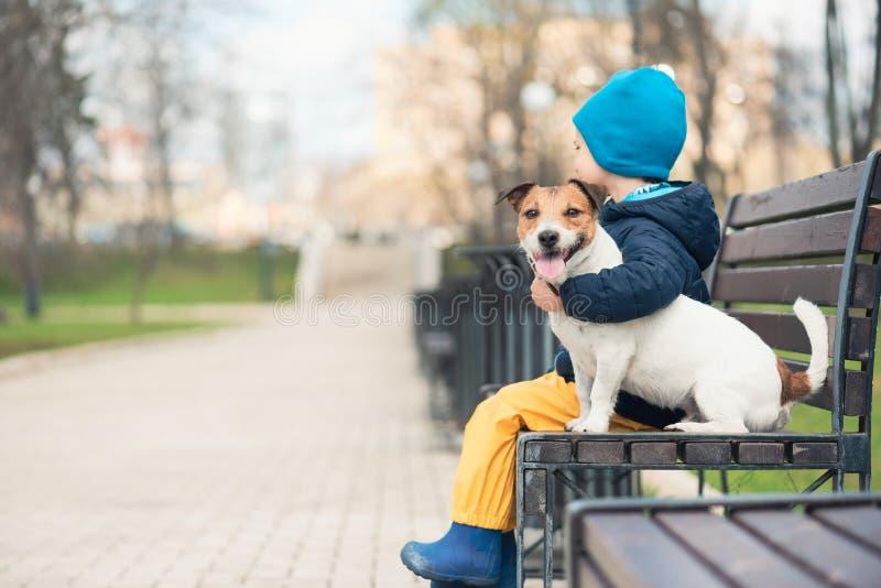 与拥抱他的爱犬的男孩的家畜概念在春天公园 免版税库存图片