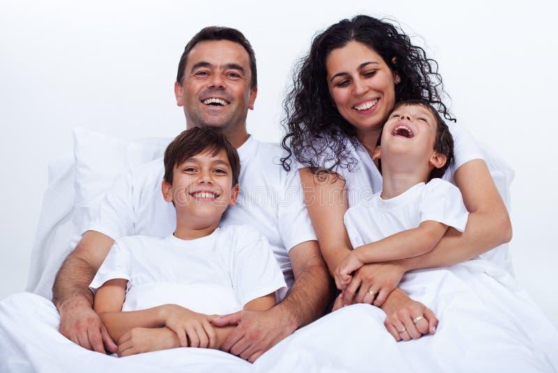 与拥抱在床上的两个男孩的愉快的家庭在一个懒惰早晨 免版税库存图片