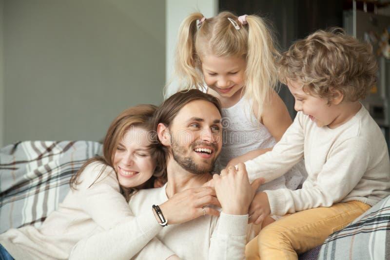 与拥抱的孩子的快乐的家庭拥抱爸爸,愉快的父亲d 免版税图库摄影