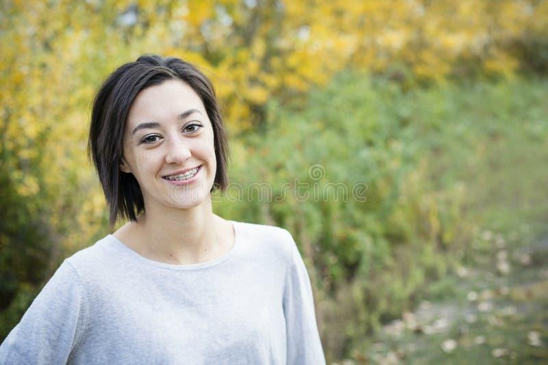 与括号的美丽的西班牙青少年的女孩画象 免版税库存照片